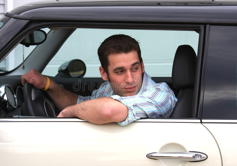 Man Driving Car. Young man looking behind his vehicle to safely back out of the driveway royalty free stock photo