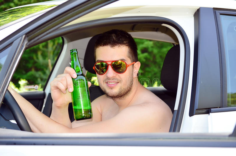 Man driving car with beer in hand. Young man driving car with beer in hand royalty free stock photos
