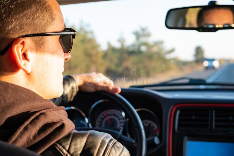 Man driving a car in rural area, backseat view. Male driver in m royalty free stock images