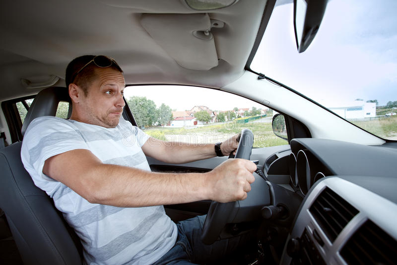 Man driving car , speeding fast. Scared man driving car very fast, focused on the driver's face royalty free stock photos