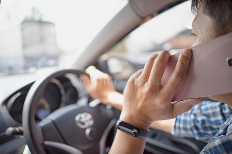 Man driving car and talking on mobile phone stock photo