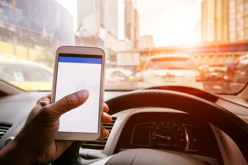 Man driving car in urban traffic and touching on smart phone ap royalty free stock image