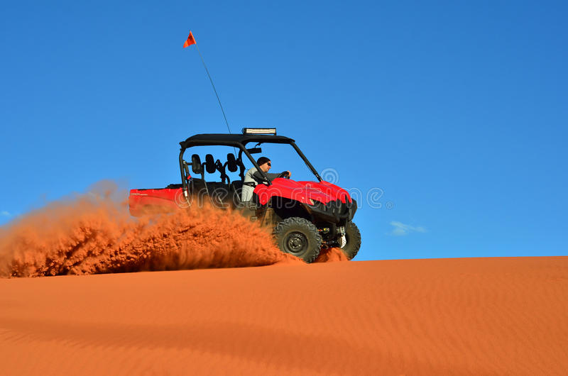 Man Driving a Four Wheeler on Sand with Blue Sky stock photo