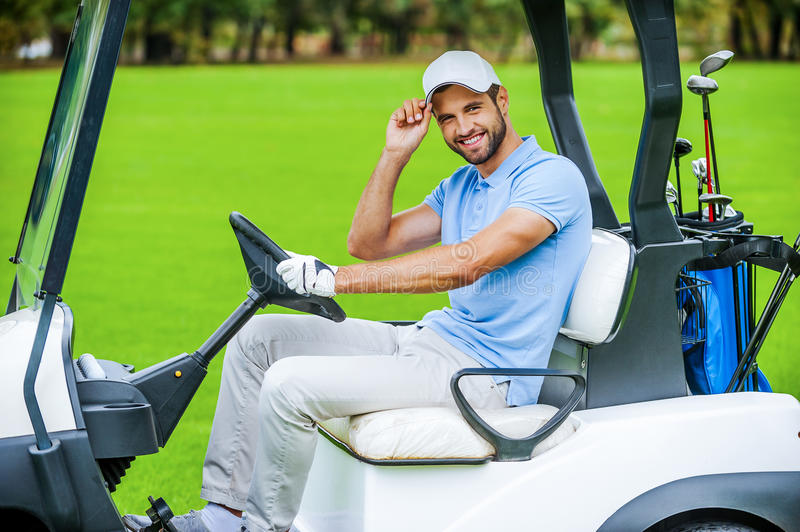 Two mature men in golf cart on golf course Stock