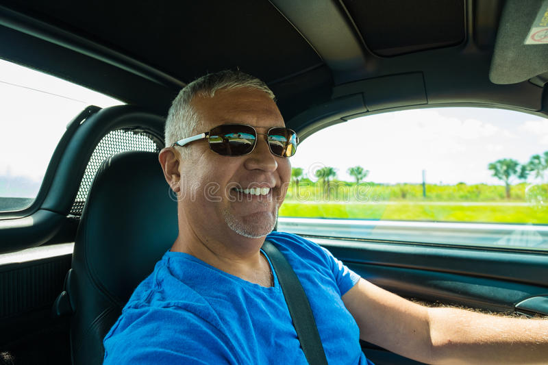Man driving. Handsome middle age man driving a convertible automobile on the highway royalty free stock images