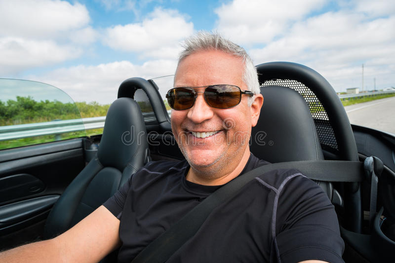 Man driving. Handsome middle age man driving a convertible automobile on the highway royalty free stock photos