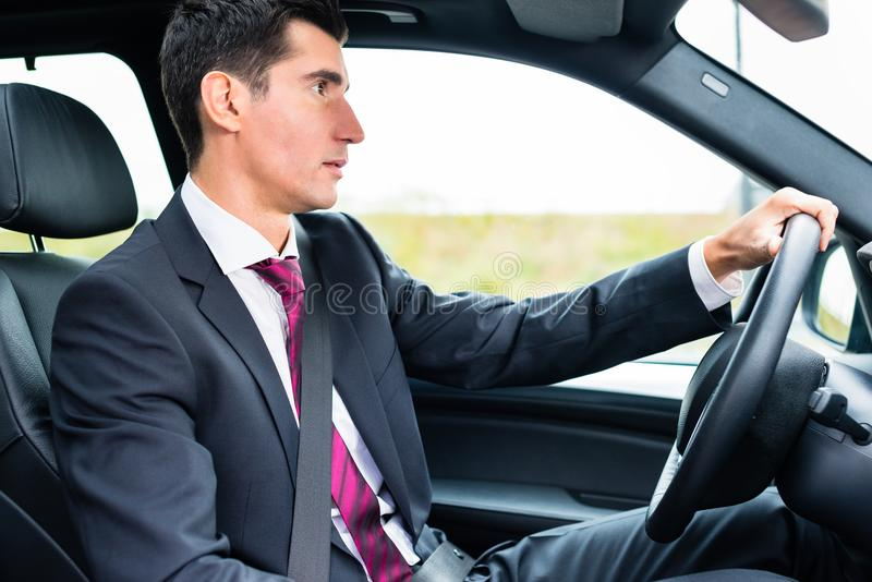Man driving in his car in business attire. Man driving his car for business travel wearing a suit stock photography