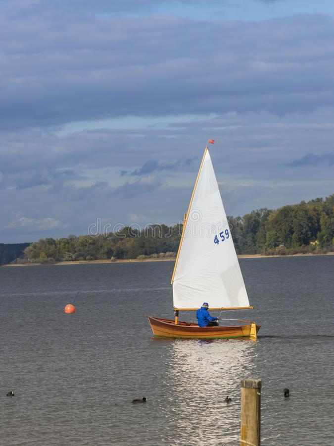 A man is driving his little sailboat over the water stock images