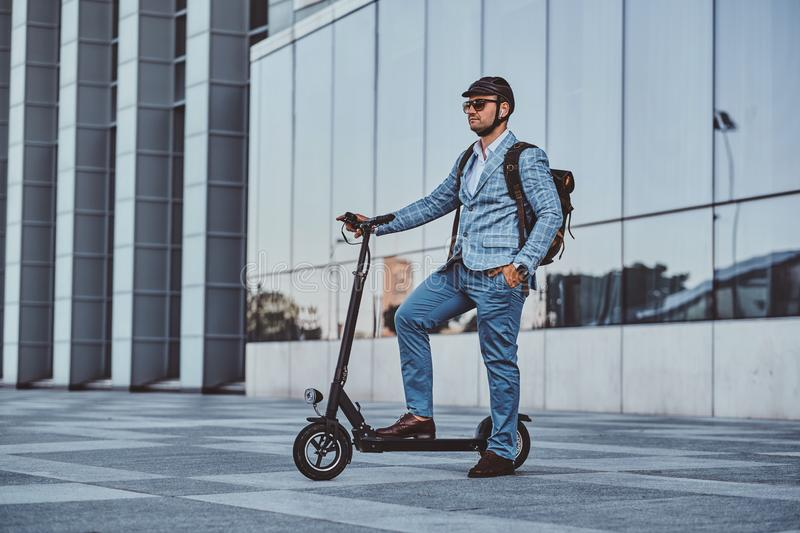 Man is driving his new electro scooter near big glass building stock image