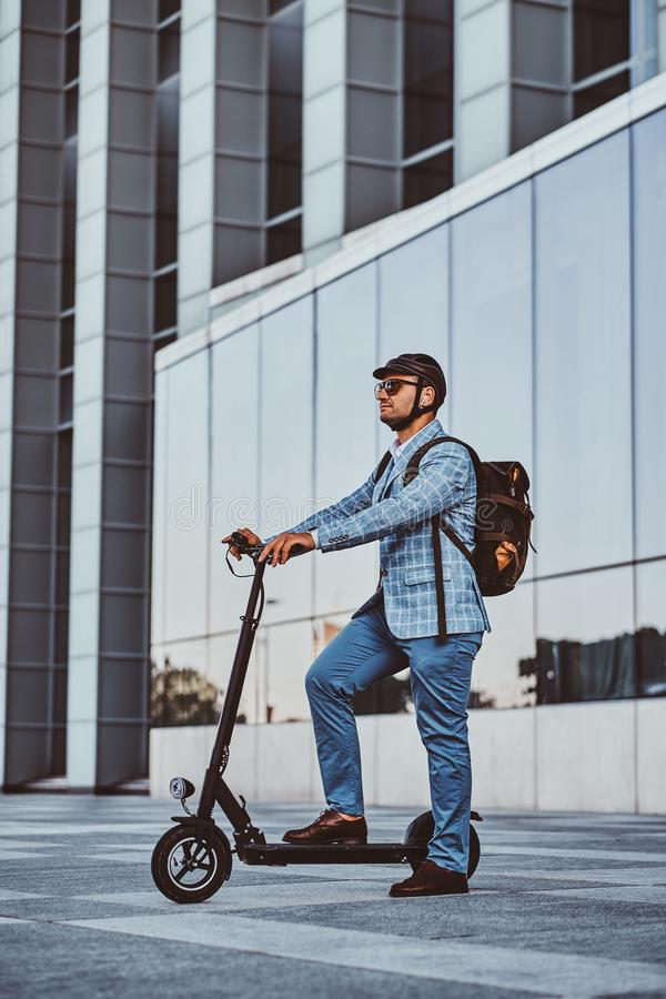 Man is driving his new electro scooter near big glass building stock photos