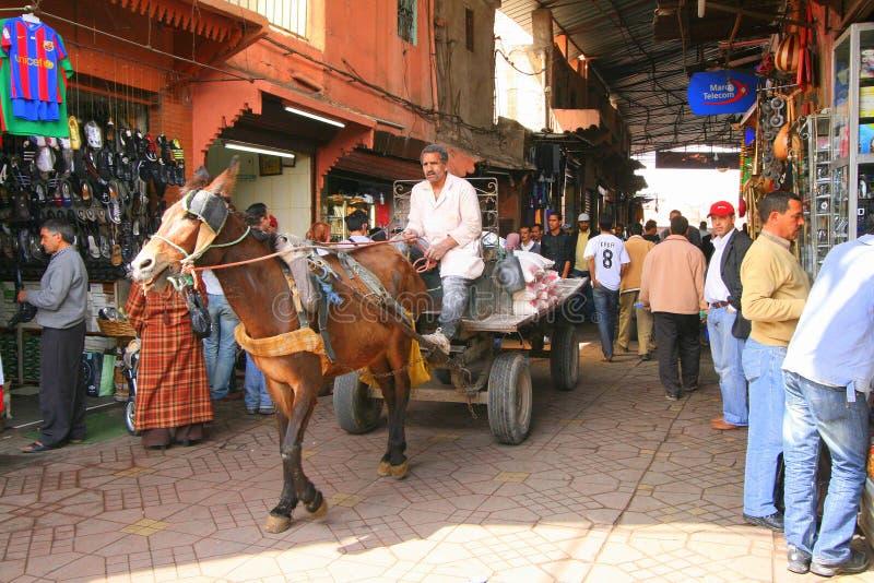 Man driving horse and cart through market royalty free stock photos