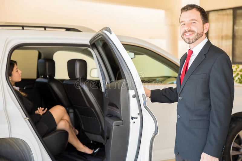 Man driving an important woman in a car. Good looking young Hispanic driver closing the door and driving a very important businesswoman in a car stock images