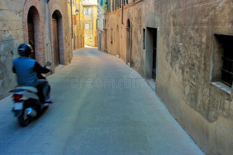 Man driving motobike blurred motion in historic center of Mon stock images