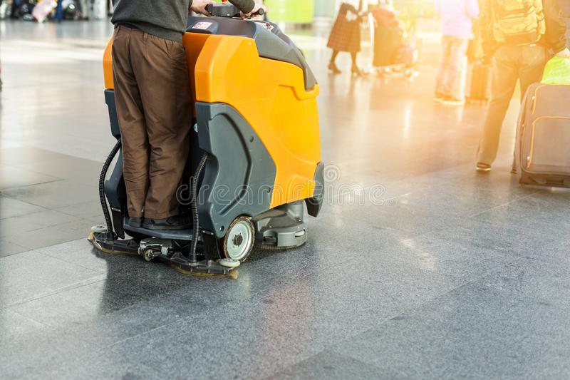 Man driving professional floor cleaning machine at airport or railway station. Floor care and cleaning service agency royalty free stock photography