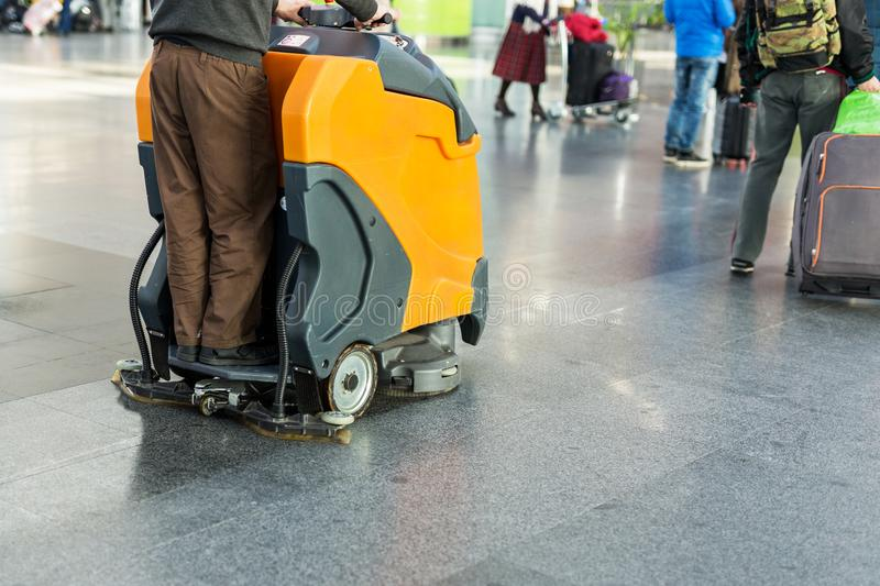 Man driving professional floor cleaning machine at airport or railway station. Floor care and cleaning service agency.  royalty free stock photo
