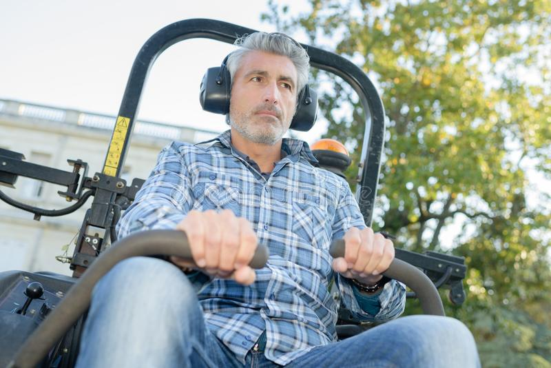 Man driving professional mower. Professional royalty free stock photography