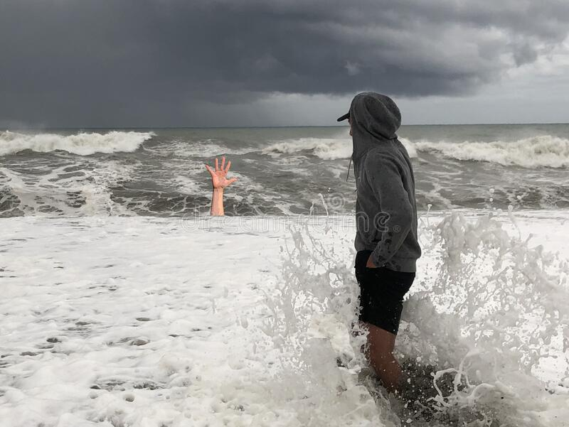 A man drowns in the sea during a storm. Hand of a drowning man from under the water. Concept: Saving a Drowning Man stock photography