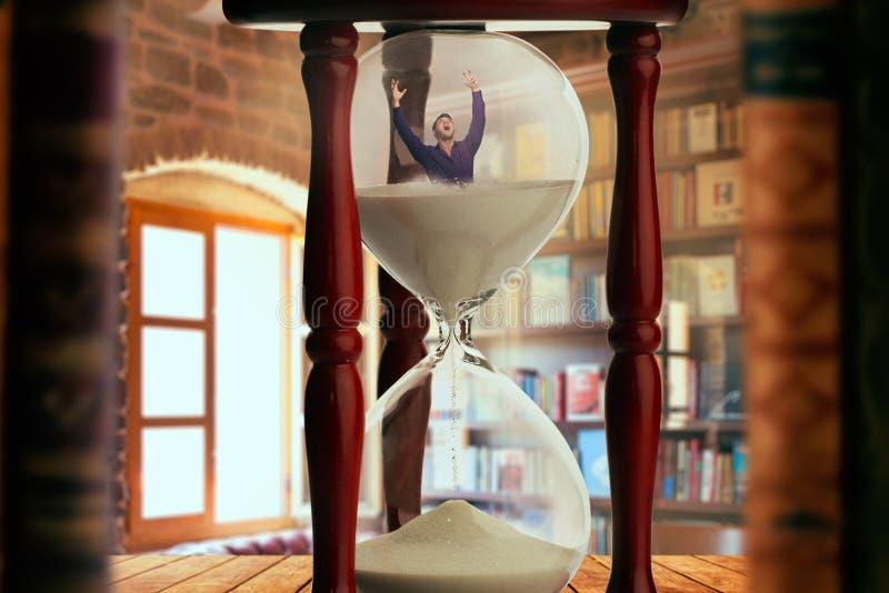 Man drunkning inom ett timglas, stopptidbegrepp fotografering för bildbyråer