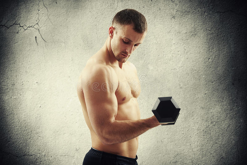 Man with dumbbell flexing biceps over concrete wall royalty free stock photography