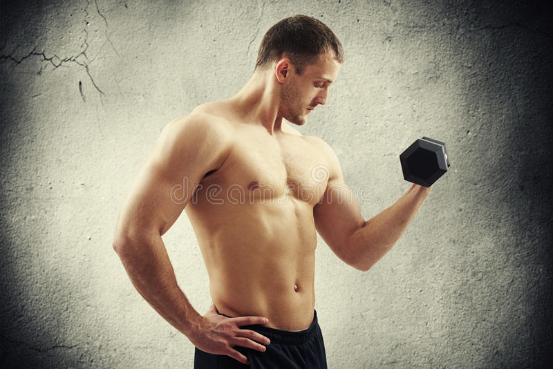 Man with dumbbell flexing biceps over cracked wall. Fit muscular bare-chested man with dumbbell in one hand is flexing biceps over cracked concrete wall stock photos