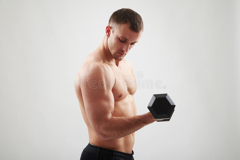 Man with dumbbell is flexing biceps stock images