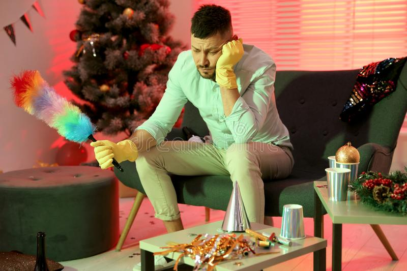 Man with dusting brush suffering from hangover in room after New Year party. Man with dusting brush suffering from hangover in messy room after New Year party stock photos