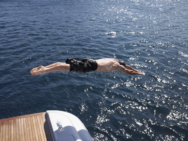 Man dykning in i havet från yachten royaltyfria foton