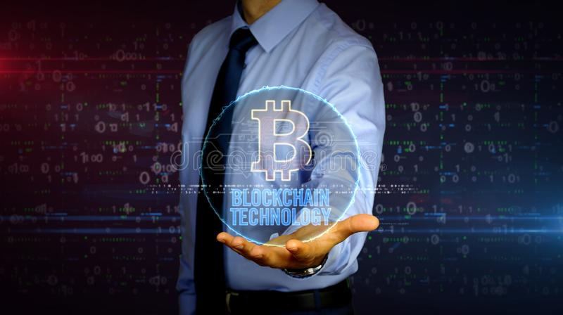 Businessman with bitcoin hologram. Man with dynamic cryptocurrency transaction and bitcoin symbol hologram on hand. Businessman with futuristic concept of royalty free stock photo