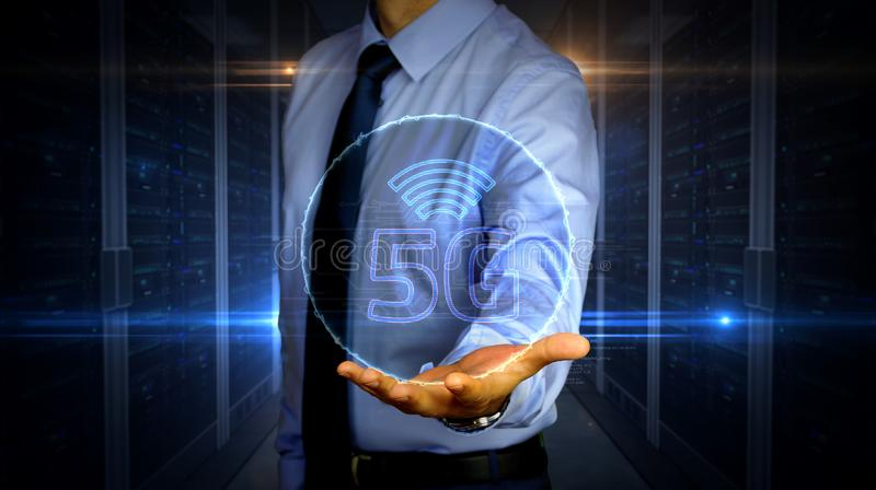 Businessman with 5G symbol hologram. Man with dynamic 5G symbol hologram on hand. Businessman and futuristic concept of mobile wireless network, communication stock photography