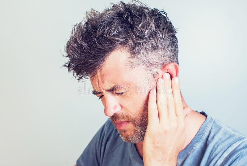 Man with earache is holding his aching ear body pain concept. On grey background royalty free stock photos