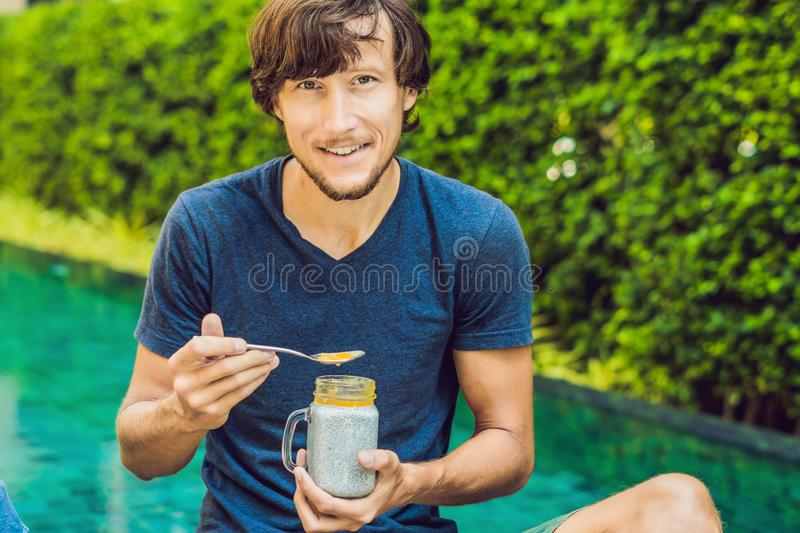 Man eat dessert with chia seeds and mangoes by the pool in the morning. healthy eating, vegetarian food, diet and people royalty free stock image