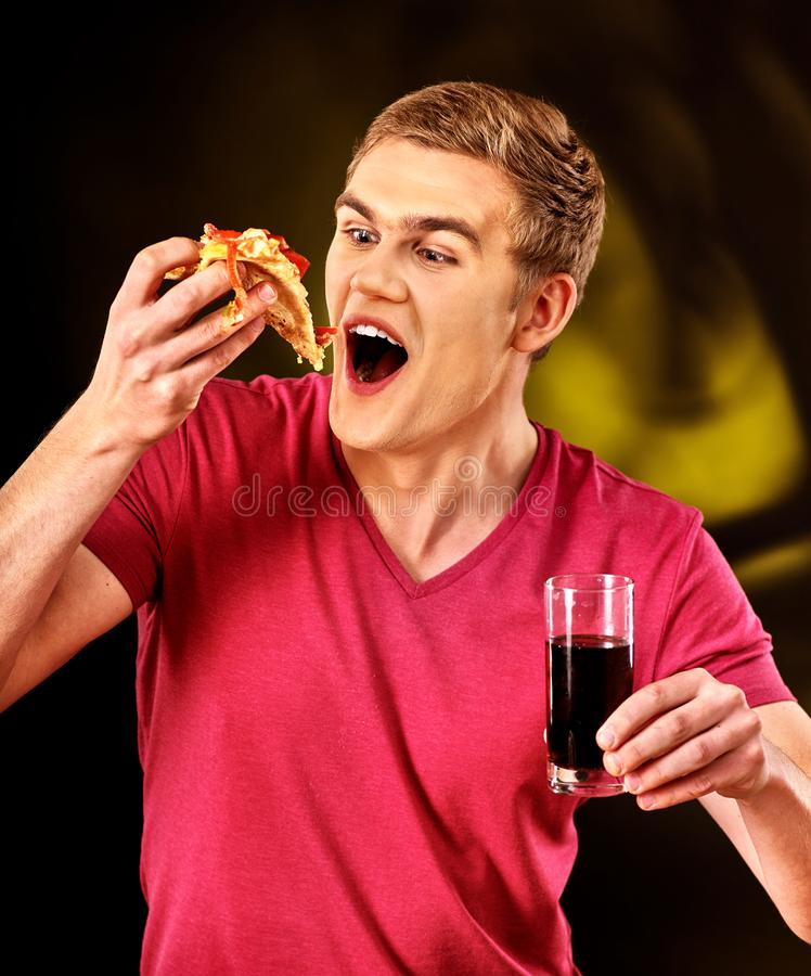 Man eat fast food pizza piece and drink cola glass. Man eat fast food pizza piece and drink glass of cola with good appetite royalty free stock image