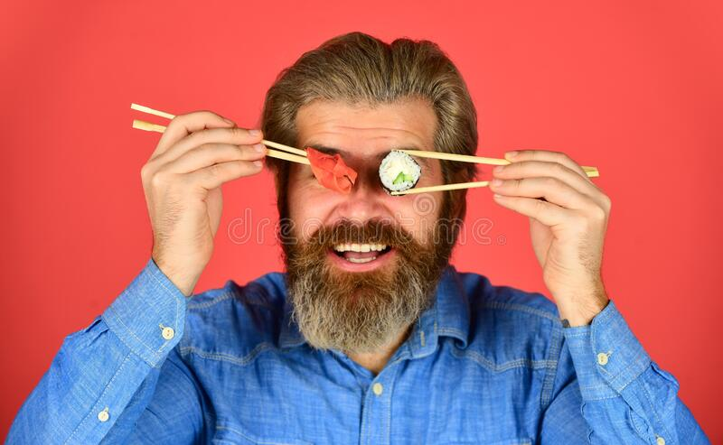 Man eat sushi chopsticks. Japanese cuisine. Asian meal. Sushi roll. Sushi rolls. Eastern culture. Bearded hipster eating. Rolls. Japanese food delivery. Pickled royalty free stock photography