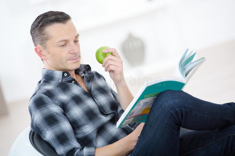 Man eating apple and reading while laying on couch. Man eating apple and reading while laying on the couch royalty free stock image
