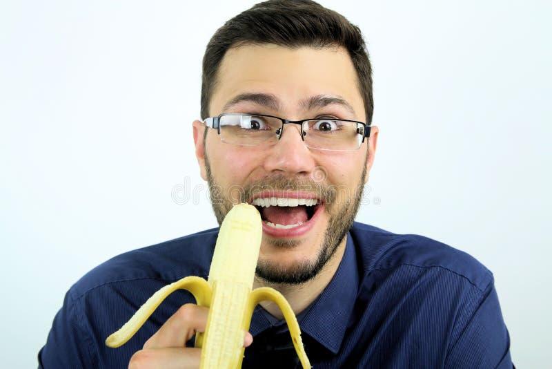 Man eating a banana. Man happy eating a banana over a white background royalty free stock image