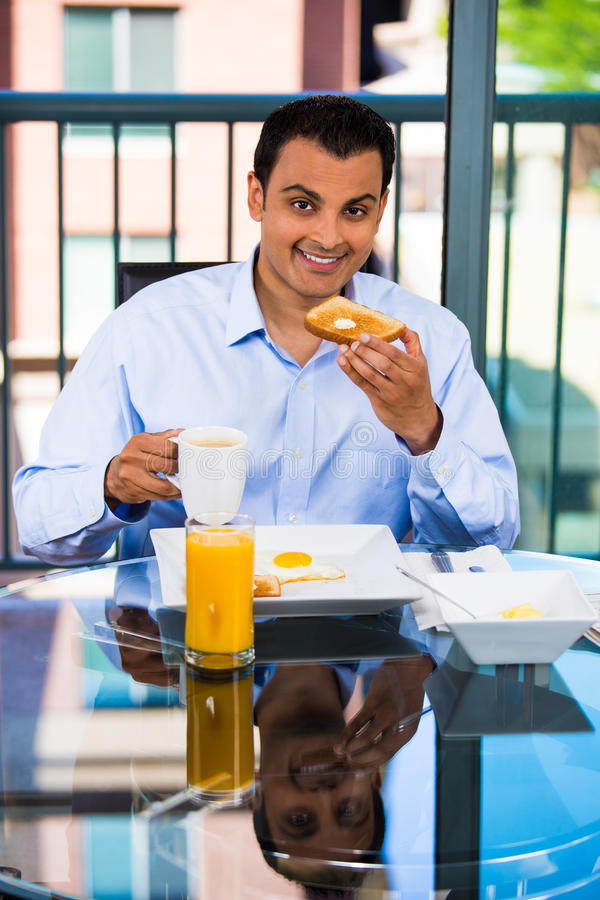 Man eating breakfast. Portrait of a happy man eating a nutritious breakfast in his home, isolated on a city background stock photo