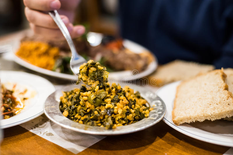 Man eating bulgur pilaf with spinach and onions stock images
