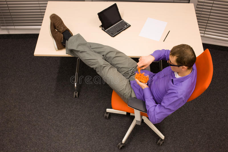 Man eating carrot in office stock images