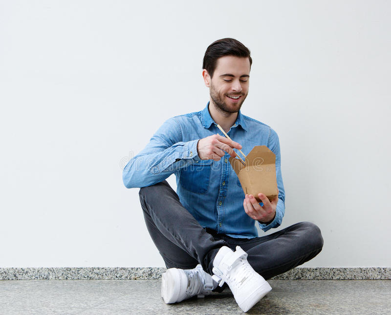 Man eating chinese food with chopsticks. Portrait of a handsome young man eating chinese food with chopsticks stock photography