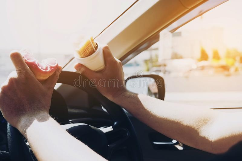 Man eating donuts and potato chip while driving car - multitasking unsafe driving concept stock images