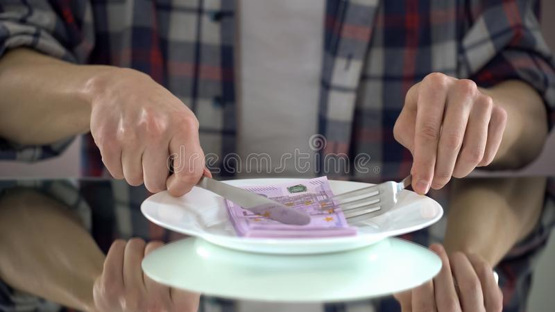 Man eating euro banknotes, wasting money, symbol of consumerism, budget for food. Stock photo royalty free stock images