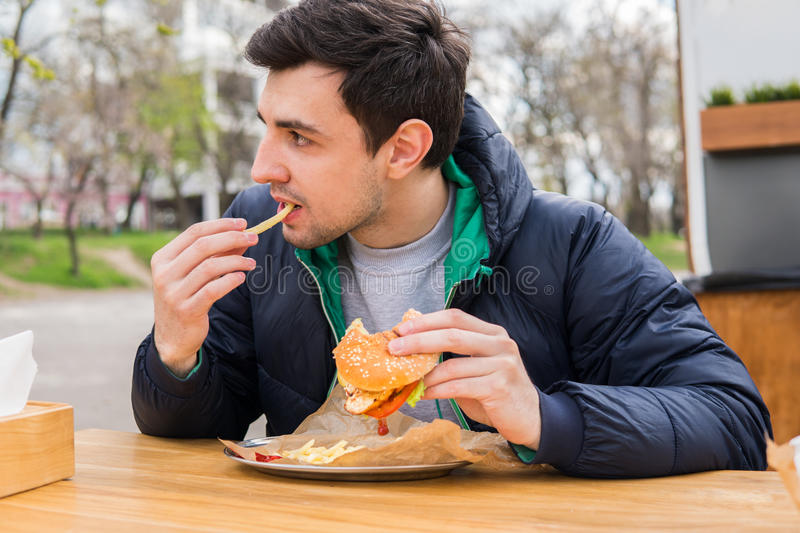 Man eating fried potatoes with a burger in street food cafe. A portrait of young man eating fried potatoes with a burger in street food cafe. Fast food eating stock image