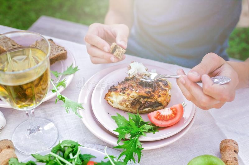 Man eating fried sea fish in the garden at the table. Dinner concept with wine in the fresh air. Fish and salads with vegetables stock photography