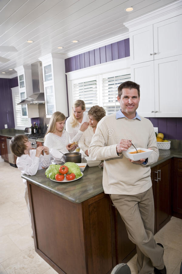 Man eating in kitchen with family in background. Mid-adult man eating lunch in kitchen with family in background royalty free stock image