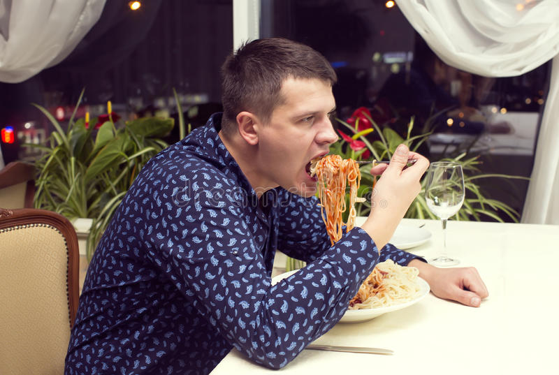 Man eating a large portion of pasta. In a restaurant stock photo