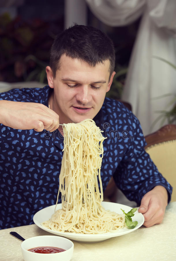 Man eating a large portion of pasta. In a restaurant stock photography