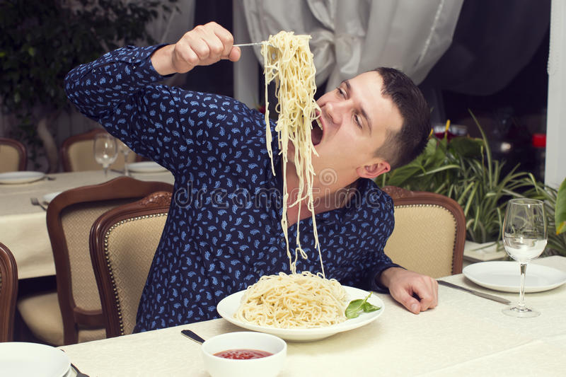 Man eating a large portion of pasta. In a restaurant stock images