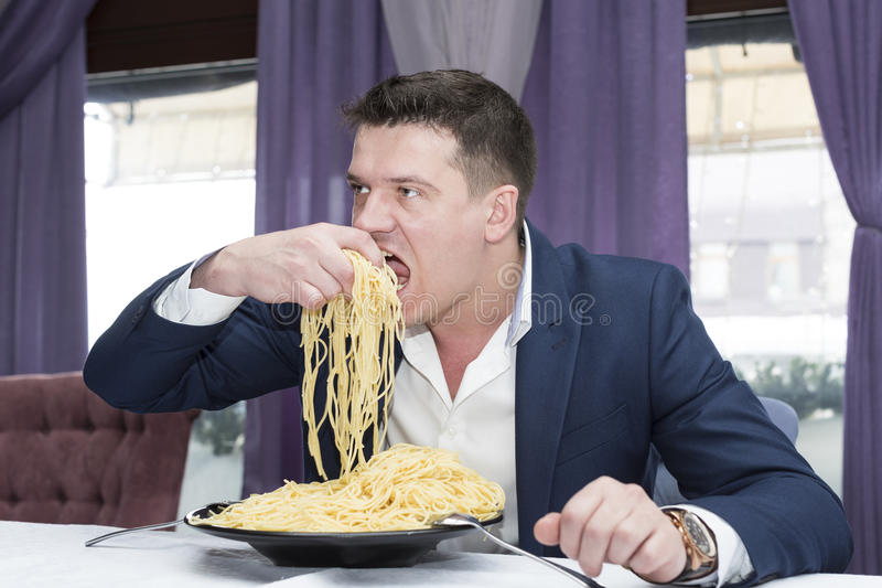 Man eating a large portion of pasta. In a restaurant royalty free stock photography