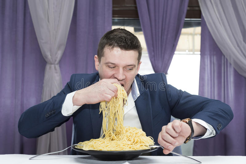 Man eating a large portion of pasta. In a restaurant stock photos