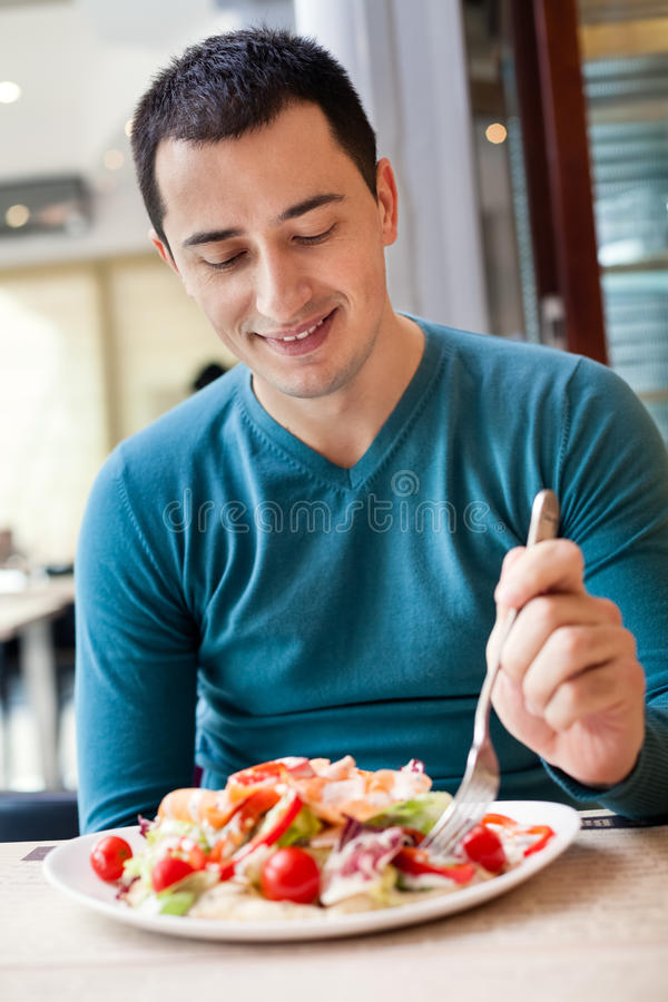 Man eating large portion of salad. At cafe royalty free stock photos